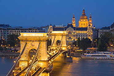 Night view of the Chain Bridge (Szechenyi Lanchid), illuminated, over the River Danube with the Gresham Hotel, St. Stephen's basilica, and the Pest side behind, Budapest, Hungary, Europe