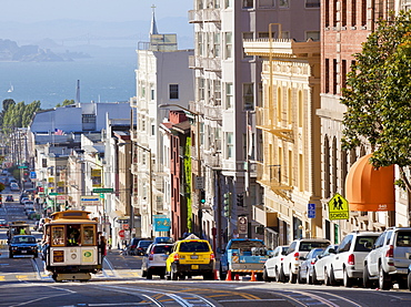 One of the famous cable cars on the Powell-Mason track, with the island of Alcatraz in the background, San Francisco, California, United States of America, North America