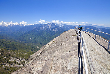 Tourist hiker, on top of Moro Rock overlooking the Sequoia foothills, looking towards Kings Canyon and the high mountains of the Sierra Nevada, Sequoia National Park, California, United States of America, North America