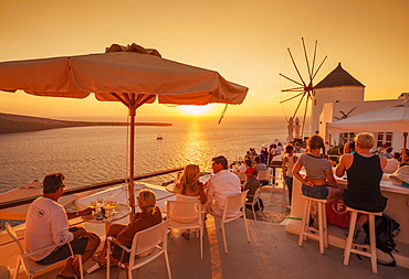 Crowded bar and windmill at sunset by the Aegean Sea, Oia, Santorini (Thira) Cyclades Islands, Greek Islands, Greece, Europe