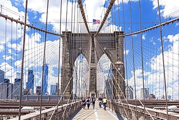 Tourists, cyclists on walkway, Brooklyn Bridge, Lower Manhattan skyline, New York skyline, New York City, United States of America, North America