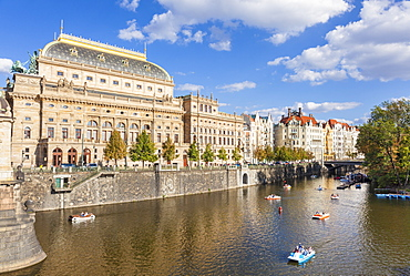 Prague National Theatre (Narodni divadlo) by the river Vltava with people in boats, Prague, Czech Republic, Europe