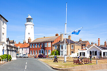 Southwold Lighthouse and houses with People sat on a bench St James Green East Cliff Southwold Suffolk England UK GB Europe