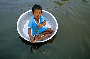 Small boy in circular metal boat, Lake Tonle Sap, Chong Kneas village, Siem Reap, Cambodia, Indochina, Southeast Asia, Asia