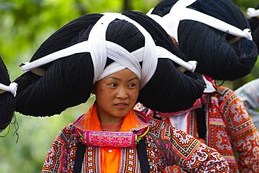 Long Horn Miao girls in traditional costumes celebrating Flower Dance Festival, Longjia village, Guizhou Province, China, Asia