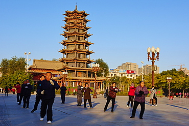 Morning exercises in front of the wooden pagoda on the main square, Zhangye, Gansu Province, China, Asia