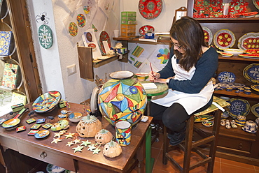 A craftswoman hand painting traditional ceramics, Erice, Sicily, Italy, Europe