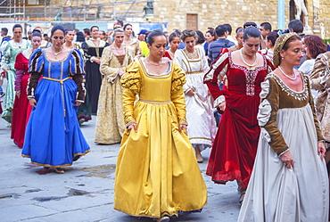 Women marching in costume dresses during Calcio Storico Fiorentino festival at Piazza della Signoria in Florence, Tuscany, Italy, Europe