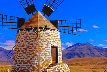 Old Windmill with volcanoes in background near Tefia, Fuerteventura, Canary Islands, Spain
