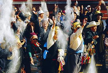 Buddhist people throwing flour into the air, symbolising the Buddha's wisdom, during the Losar (Tibetan New Year), Bodhnath, Katmandu, Nepal