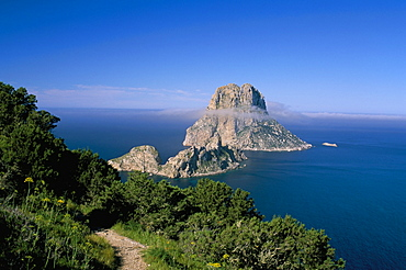 The rocky islet of Es Vedra surrounded by mist, with pine trees in foreground, near Sant Antoni, Ibiza, Balearic Islands, Spain, Mediterranean, Europe
