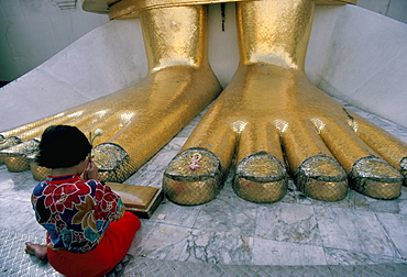 Woman praying at the feet of the Buddha in the temple of the Standing Buddha, Wat Intrawiharn, Bangkok, Thailand, Southeast Asia, Asia