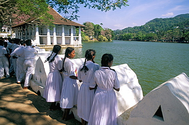 Girls standing on the edge of the artificial lake, Kandy, Sri Lanka, Asia