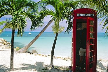English telephone box on the beach, Dickenson's Bay, North-East coast, Antigua, West Indies