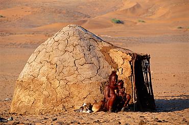 Himba woman & child beside traditional house, Kaokoland, Namibia
