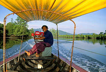 Long tail boat and driver on the river, Thailand, Southeast Asia, Asia