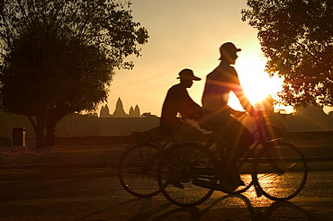 Sunrise, cyclists outside temple complex, Angkor Wat Temple, Cambodia, South East Asia