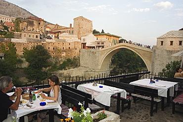 Restaurant overlooking the Stari Most Peace Bridge on Neretva River, Mostar, Bosnia, Bosnia-Herzegovina, Europe