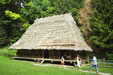 Tourists visiting traditional thatched roof house in the Museum of Folk Architecture and Rural Life, Old Town, UNESCO World Heritage Site, Lviv, Ukraine, Europe