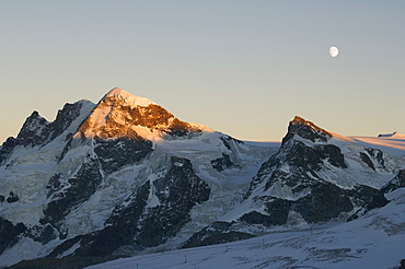 Moon rising over the Klein Matterhorn, 3883m and Breithorn 4164m mountains, Zermatt Alpine Resort, Valais, Switzerland, Europe