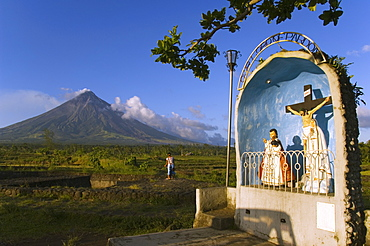 Volcanic cone with plume of smoke of Mount Mayon, 2462m, and grotto or wayside shrine, Bicol Province, Luzon Island, Philippines, Southeast Asia, Asia