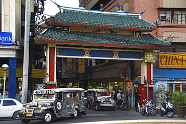 Jeepney driving under Chinatown Gate, Manila, Philippines, Southeast Asia, Asia