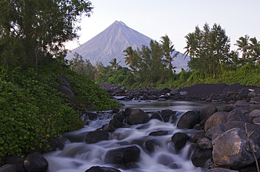 Waterfall beneath Mount Mayon, 2462m, a volcanic cone with plume of smoke, Bicol Province, southeast Luzon, Philippines, Southeast Asia, Asia