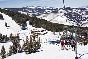 Skiers being carried on a chair lift to the back bowls of Vail ski resort, Vail, Colorado, United States of America, North America