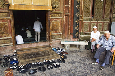 Men praying and shoes left outside at The Great Mosque located in the Muslim Quarter home to the city's Hui community, Xian City, Shaanxi Province, China, Asia