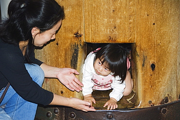 Child crawling though hole in wooden column to reach Nirvana, Todaiji (Big Buddha) Temple, constructed in the 8th century, Nara City, Nara Prefecture, Honshu Island, Japan, Asia