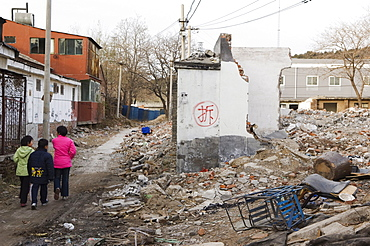 Girls walking in a neighbourhood Hutong partially destroyed and marked for demolition, Beijing, China, Asia
