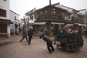 A woman pulling a cart of charcoal bricks on an old street in Shantang district of Suzhou, Jiangsu Province, China, Asia