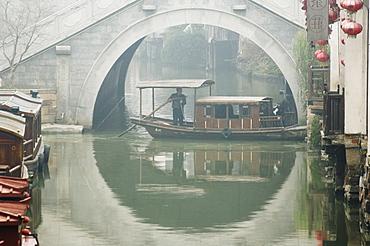 Traditional stone arched bridge and river boat in Shantang water town, Suzhou, Jiangsu Province, China, Asia
