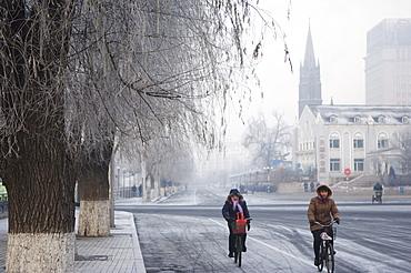Cyclists in a winter wonderland and Catholic church in Jilin City, Jilin Province, Northeast China, China, Asia