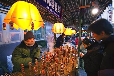 A street market selling local snacks and sweet hawthorne on sticks, Daoliqu area, Harbin, Heilongjiang Province, Northeast China, China, Asia