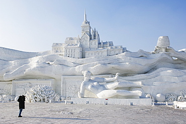 A lone person photographing a giant sculpture at Snow and Ice Sculpture Festival on Sun Island Park, Harbin, Heilongjiang Province, Northeast China, China, Asia