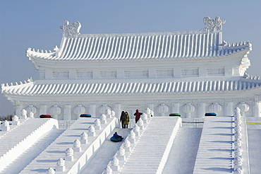 A boy slides down a giant replica sculpture of Beijing's Forbidden City at the Snow and Ice Sculpture Festival on Sun Island Park, Harbin, Heilongjiang Province, Northeast China, China, Asia