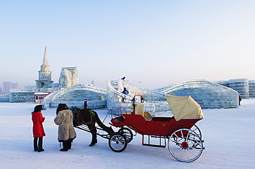 A horse and carriage ride and snow and ice sculptures at the Ice Lantern Festival, Harbin, Heilongjiang Province, Northeast China, China, Asia