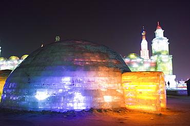 An igloo ice sculpture illuminated at night at the Ice Lantern Festival, Harbin, Heilongjiang Province, Northeast China, China, Asia