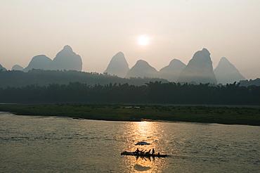 Tourist boat sailing through karst scenery at sunrise on the Li river (Lijiang) in Yangshuo, near Guilin, Guangxi Province, China, Asia