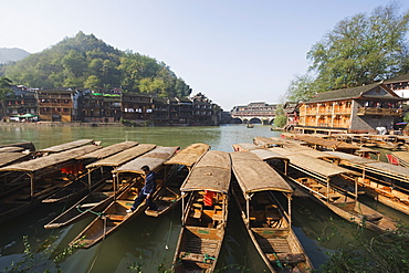 Boats tied up on a river in the old town of Fenghuang, Hunan Province, China, Asia