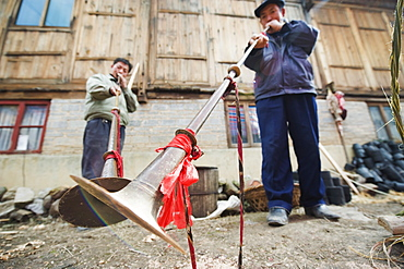 Men playing traditional horn instruments at a Lunar New Year festival in the Miao village of Qingman, Guizhou Province, China, Asia
