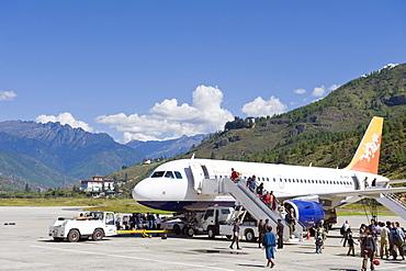 Passenger plane at Paro International Airport, Paro Rinpung Dzong in the distance, Paro, Bhutan, Himalayas, Asia