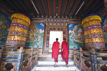 Monks walking between prayer wheels at Trongsa Dzong (Chokhor Raptentse) dating from 1648, Bhutan Asia