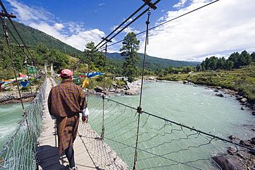 Local man crossing a bridge, Bumthang, Chokor Valley, Bhutan, Asia