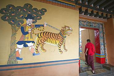 A monk walks past a tiger painting at Paro Rinpung Dzong dating from 1644, Paro, Bhutan, Asia