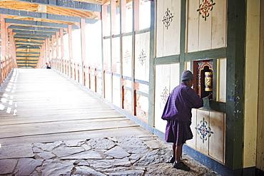 Local man spinning a prayer wheel, Punakha Dzong dating from 1637, Punakha, Bhutan, Asia