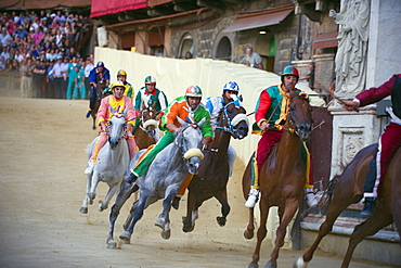 Riders racing at El Palio horse race festival, Piazza del Campo, Siena, Tuscany, Italy, Europe