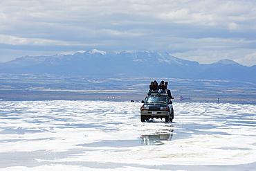 Four wheel drive (4WD) with tour group on Salir de Uyuni, salt flats, Bolivia, South America