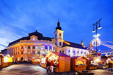 Christmas market in Plaza Piata Mare, City Hall and Baroque Jesuit Church, Sibiu, Romania, Europe